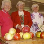 The Bennet sisters displaying apples at Apple Festival 1999. On the left is Evelyn Lee, who is still an active Pie Lady. In the middle is Mary Mollett, who wrote 2 lovely cook books, AN APPLE A DAY COOKBOOK, just based on apples.. Daughter, Terry Manuck, is still selling those cookbooks. On the right is the late, June Stevens, who raised and sold beautiful flowers near the Beaver Point Hall. Photo by Derek Lundy.