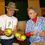Harry Burton and Jill Willmott are discussing which of these apples best represents the apple variety, Bramley Seedling. This happens when more than one bag of a variety are submitted. Photo by Jan Mangan